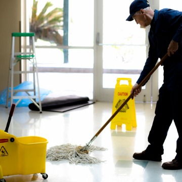 Janitor mopping a floor, providing Cleaning Services in Peoria IL