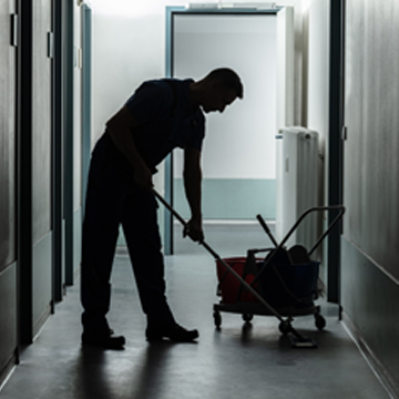 Man performing office cleaning services in Peoria IL by mopping hallway