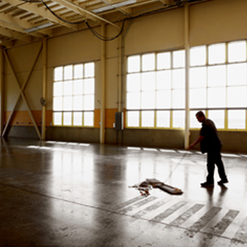 Man from industrial cleaning company in Peoria IL sweeping floor of warehouse
