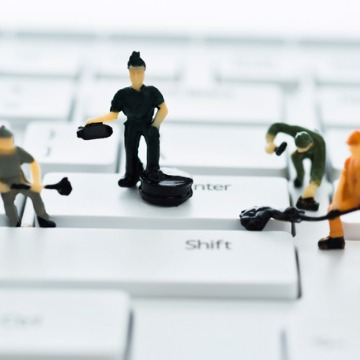 Little toy men cleaning a keyboard and representing Commercial Cleaning Companies