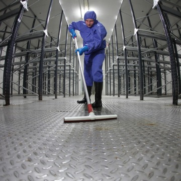 A Janitor in Pekin IL mopping the floor of a manufacturing facility