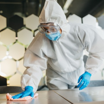 A cleaner wiping down a table surface during Disinfection Services for Pekin IL